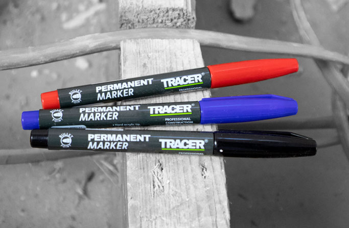 Black, Blue and Red Markers on a wooden beam
